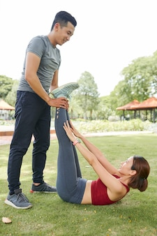 Fitnesstrainer meewerkende cliënt