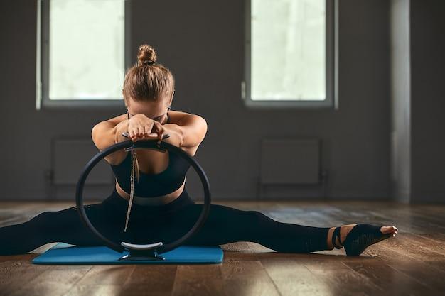 Fitnesstrainer met een mooi figuur poseert voor de camera tijdens een training in de sportschool met een ispanderring