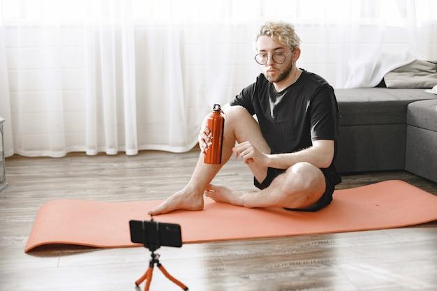 Fitnesstrainer of videoblogger die zich uitstrekt. de man filmt zichzelf thuis op de smartphonecamera.