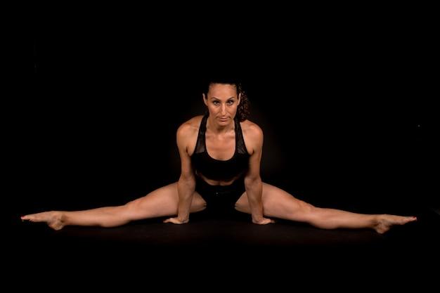 Fitnessvrouw die strekoefeningen doet