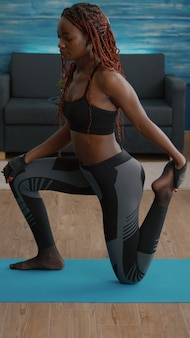 Fitnessvrouw met zwarte huid die fitnesstraining in de woonkamer beoefent en beenoefening doet op een...
