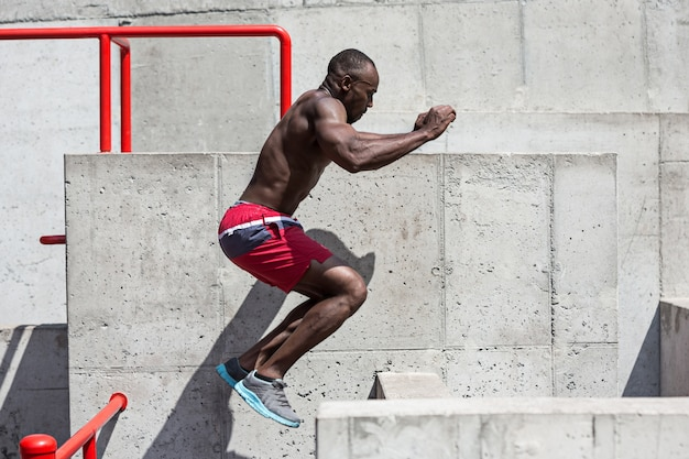 Fitte atleet die oefeningen doet in het stadion. afro man buiten in de stad. springsport oefeningen. fitness, gezondheid, lifestyle concept