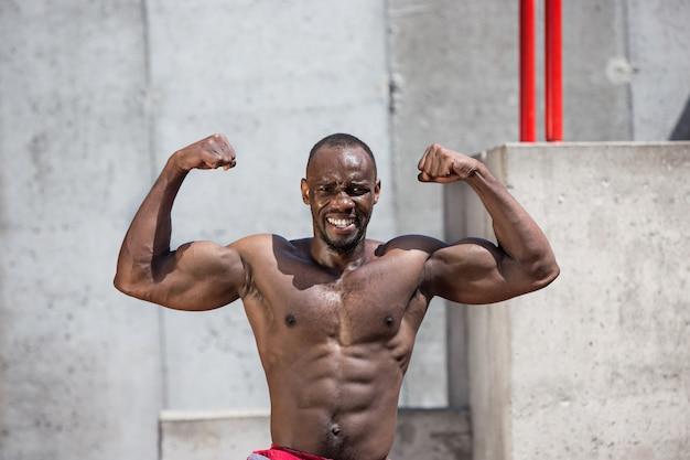 Fitte atleet die oefeningen doet in het stadion. afro man buiten in de stad. trek sportoefeningen uit. fitness, gezondheid, lifestyle concept