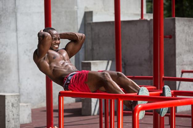Fitte atleet die oefeningen doet in het stadion. afro man buiten in de stad. trek sportoefeningen uit.
