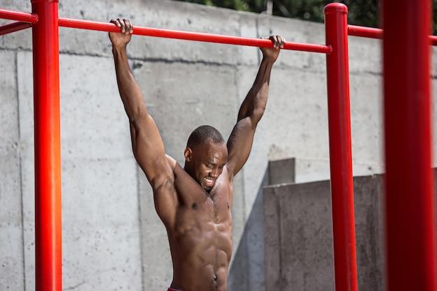 Fitte atleet die oefeningen doet in het stadion. afro of afro-amerikaanse man buiten in de stad