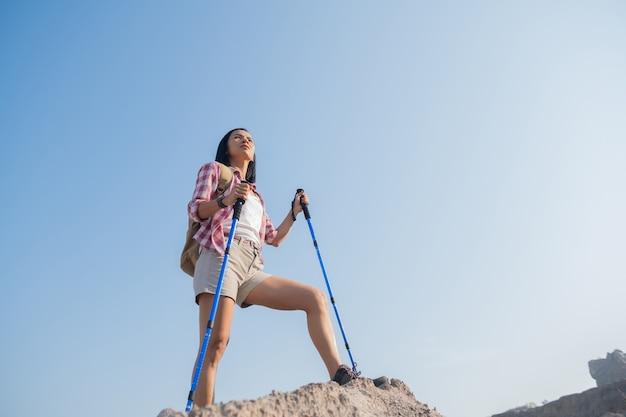 Fitte jonge vrouw wandelen in de bergen staande op een rotsachtige topkam met rugzak en paal uitkijkend over landschap.