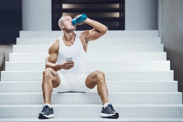 Fitte man die aan een witte trap zit en drinkt uit een blauwe shaker