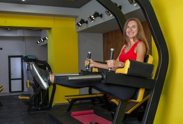 Fitte slanke vrouw in sportkleding oefent het optillen van de benen voor de buikspieren in de sportschool