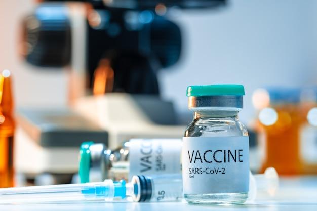 Flacon met covid-19-vaccin naast een microscoop