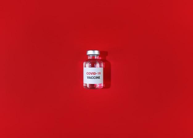 Flacon met covid 19 vaccin op een rode achtergrond. medisch eenvoudig plat leggen.