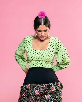 Flamenca die neer met roze achtergrond kijkt