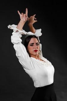 Flamenca met armen omhoog op zwarte achtergrond