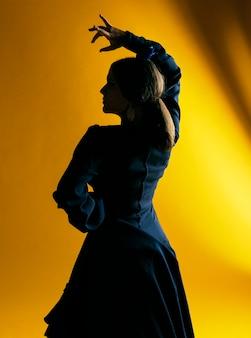 Flamenca-vrouw die hand met achtergrondverlichting opheft