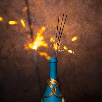 Flaming bengalen lichten in blauwe fles drinken