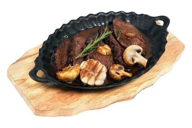 Flanklapje vlees met champignons gekookt in ovale gietijzeren schaal, staande op een houten bord, studio-opname, geïsoleerd op een witte achtergrond.