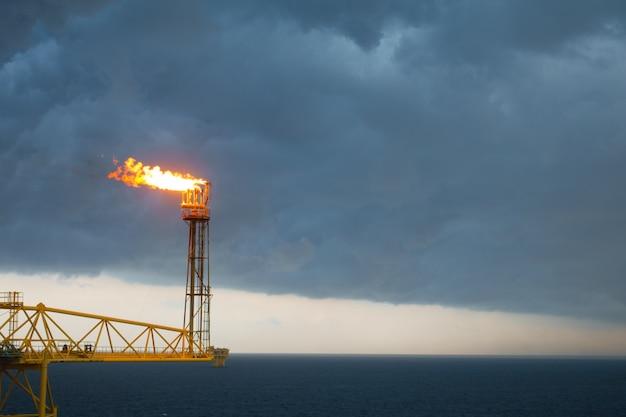 Flare-stack en flare-brug tijdens het verbranden van giftig gas en vrijkomen van de druk