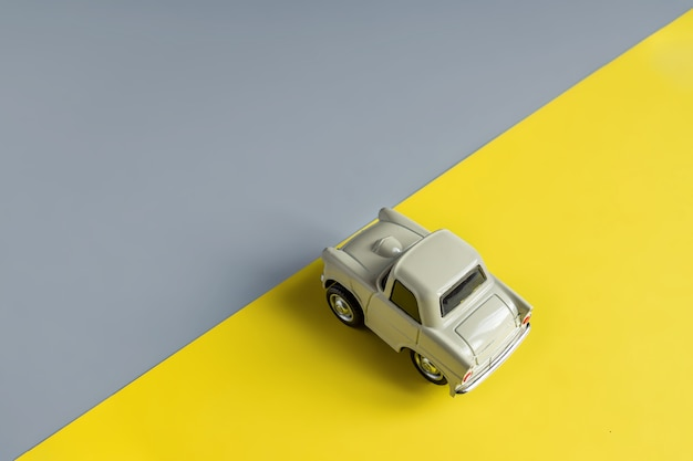 Flat lay in een trendy 2021 nieuwe kleuren. verlichtend geel en ultiem grijs. kleur van het jaar 2021. retro speelgoedauto op grijze achtergrond met kopie sapce.