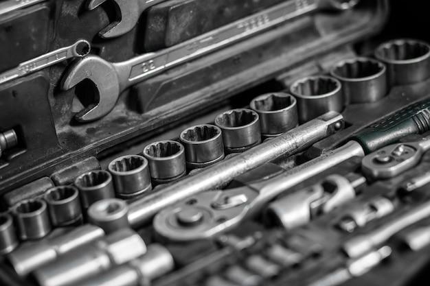 Flat lay metalen gereedschappen: sleutels, ratel, een set verwisselbare koppen van verschillende maten en ander gereedschap bevinden zich in de gereedschapskist, een bovenaanzicht.
