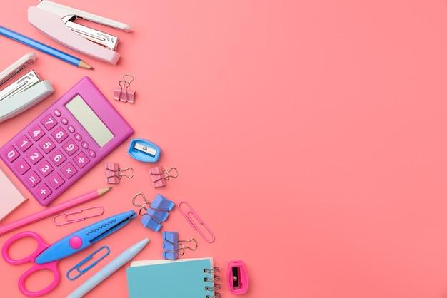Flat lay top view foto van schaar, potloden, paperclips, rekenmachine, notitie, nietmachine en notitieblok