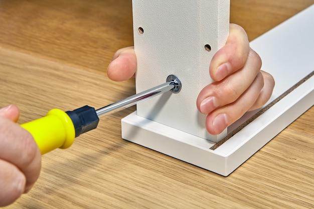 Flat pack meubelmontage, assembler zet nokvergrendeling vast met handschroevendraaier.