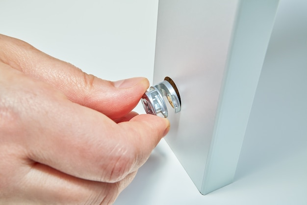 Flat pack meubelmontageservice aan huis, meubelmonteur voegt moer in.