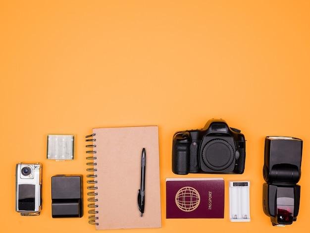 Flatlay-accessoires van een reisblogger op pasteloranje achtergrond. dslr en actiecamera, flitser, oplader met batterij, papieren notitieboekje en paspoort