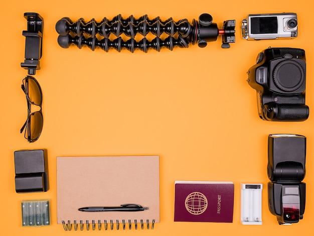 Flatlay-accessoires van een reisblogger op pasteloranje achtergrond. dslr en actiecamera, flitser, oplader met batterij, papieren notitieboekje, statief en paspoort