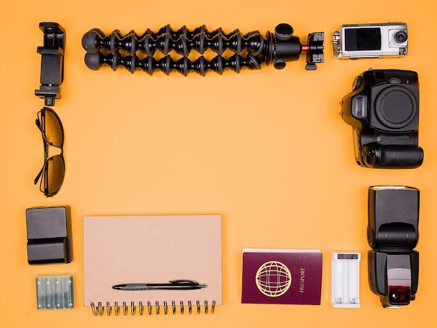 Flatlay-accessoires van een reisblogger op pasteloranje achtergrond. dslr en actiecamera, flitser, oplader met batterij, papieren notitieboekje, zonnebril, statief en paspoort. bovenaanzicht