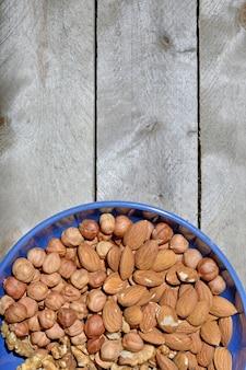 Flatlay. blauwe kop met noten op een houten achtergrond