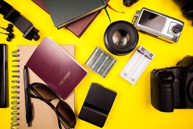 Flatlay bovenaanzicht van reiziger blogger kit op gele achtergrond in studiop foto. er zijn een paspoort, boeken, camera met lens, papier en zonnebril naast andere accessoires