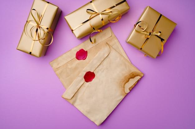 Flatlay-compositie met kerstmanlijst en ingepakte geschenkdozen op paarse achtergrond bovenaanzicht