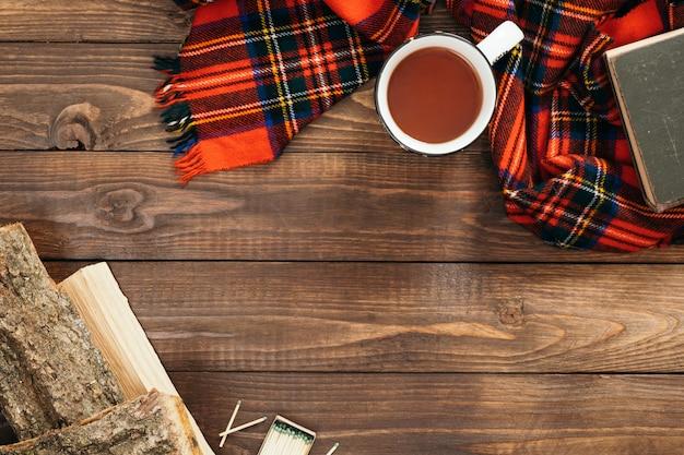 Flatlay compositie met rode sjaal, kopje thee, brandhout, boek op houten bureau tafel.