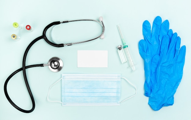 Flatlay dokterswerkplaats met stethoscoop en met masker en met spuit en ampullen met blocnote