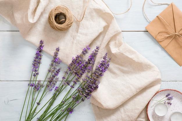 Flatlay lavendel bloemen, pastel beige deken, touw, kaarsen