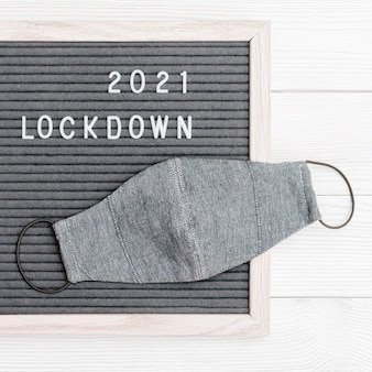 Flatlay letterbord met berichttekst lockdown 2021 en beschermend gezichtsmasker. vergrendel het laadconcept.