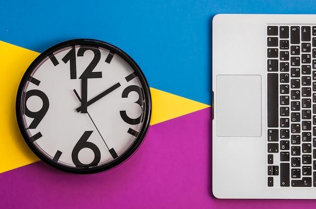 Flatlay met klok en toetsenbord van laptop op drie tone achtergrond.