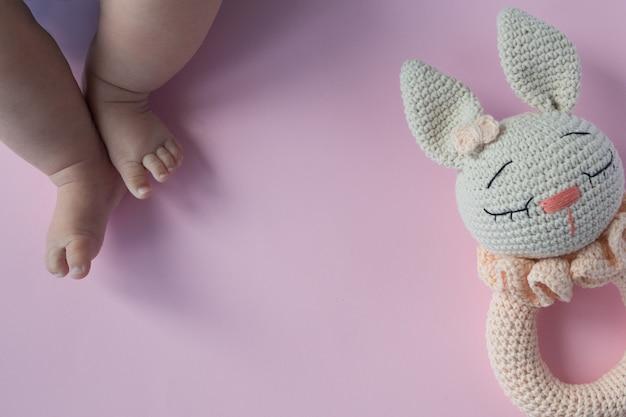 Flatlay met mollige pasgeboren babybenen en gebreide rammelaar in de vorm van een konijn.