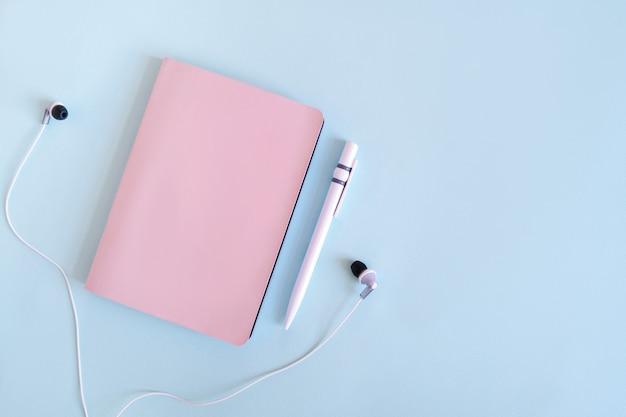 Flatlay met notitieblok, pen en koptelefoon. planning van uw bedrijf. roze notebook op een blauwe achtergrond