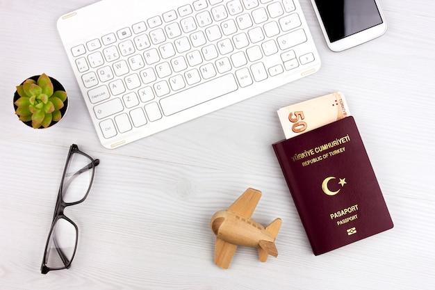 Flatlay met turks paspoort, vliegtuig en geld