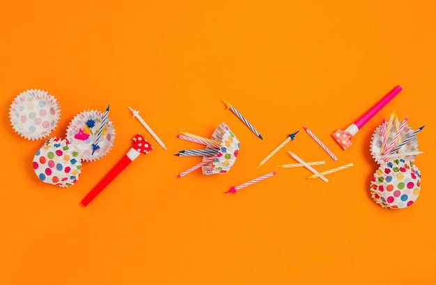 Flatlay met verschillende feestaccessoires: hoorns, kaarsen, cupcake liners etc.