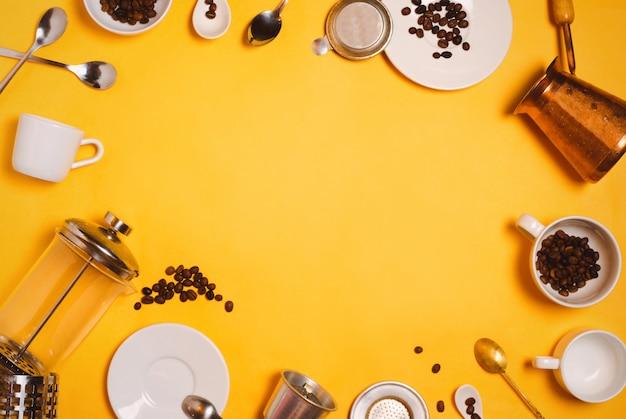 Flatlay met verschillende koffiezetaccessoires, apparatuur en keukengerei: cezve, franse pers, vietnamees phin-filter enz. op geel