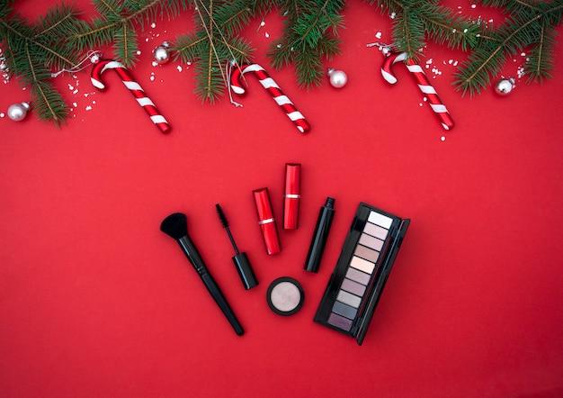 Flatlay samenstelling met make-up cosmetische producten kerst decor op rode achtergrond beauty banner