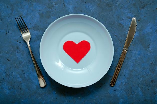 Flatlay schattig compositie rood voddenhart in een blauwe plaat met een mes en een vork aan de zijkanten op een donkerblauwe achtergrond. gelukkige verjaardag of gelukkige valentijnsdag of andere universele groeten.