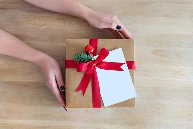 Flatlay vakantie geschenkdoos aanwezig in handen van de vrouw op houten achtergrond voor wintervakantie, kerstmis of nieuwjaar