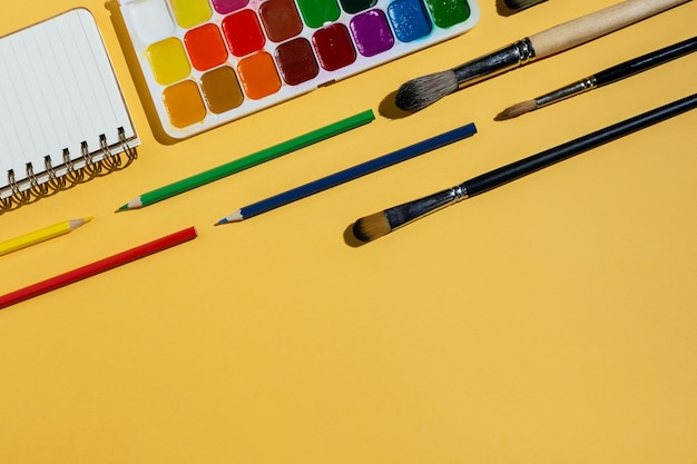 Flatlay van aquarellen, penselen, notitieboekjes en ander briefpapier en kunstbenodigdheden op geel