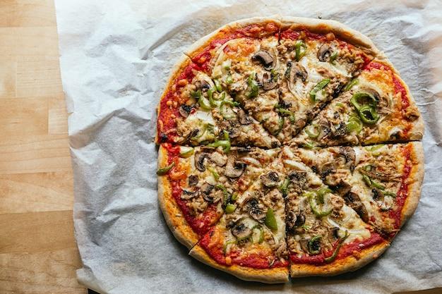 Flatlay van een heerlijke huisgemaakte italiaanse pizza met kaas, tomaten, champignons en groene paprika