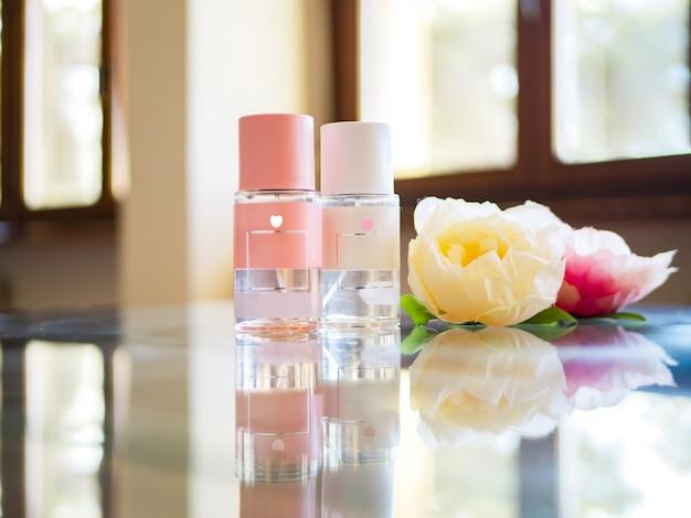 Flatlay van flessen parfum met pioenen