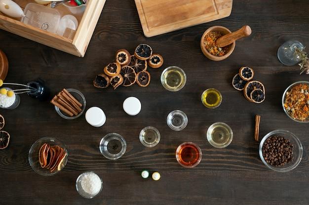 Flatlay van glaswerk van verschillende afmetingen met etherische oliën, koffiebonen, gedroogd fruit en bloemen voor het maken van natuurlijke cosmetische producten zoals zeep
