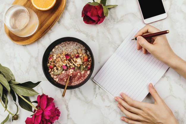 Flatlay van handen van de vrouw met een notebook en telefoon, veganistische smoothie kom met chia pudding gegarneerd met muesli, kiwi, pijnboompitten en rozenknoppen en peon bloemen op marmer, gezond ontbijt concept