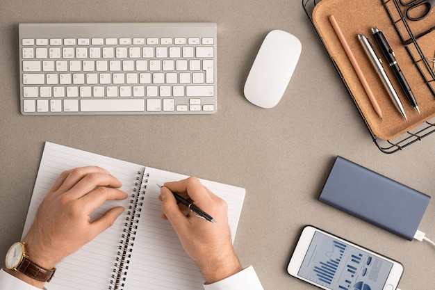 Flatlay van handen van jonge elegante makelaar met pen over blanco pagina's van geopende notitieblok het maken van aantekeningen tussen verschillende kantoorbenodigdheden